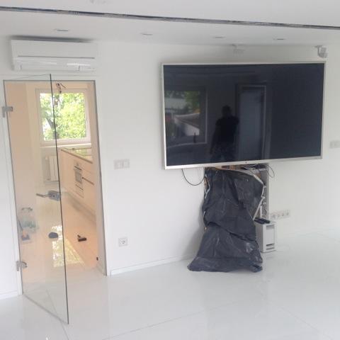 LG LED TV 213cm v pracovni. Pod TV (za mechom) sa nachádza dátový rozvádzač (rack)